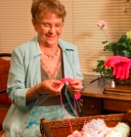 An older woman sitting knitting